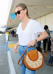 January Jones accessorized with a summer-chic raffia and leather shoulder bag by Chloe during a flight.