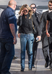 Jennifer Aniston teamed her shirt with classic blue jeans.