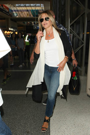 Jennifer Aniston looked perfectly comfy in jeans and a white shirt while catching a flight at LAX.