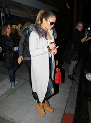 Jennifer Lopez contrasted her glamorous coat with edgy work boots by Timberland.