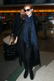 Jessica Chastain covered up in black knee-high boots and a long coat for a flight out of LAX.