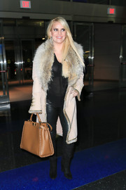 Jessica Simpson was spotted at JFK looking glam in a fur-trimmed coat.