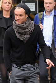 He is wearing a very layered scarf around his neck. This is a great scarf because it is versatile and is able to keep Jude warm without the hassle of a heavy winter coat.