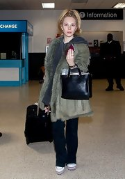 Juno Temple opted for a funky '70s-style suede jacket with fur trim for her travel look at LAX.