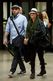 Kaley Cuoco accessorized her low-key travel gear with an olive scarf and a straw fedora.