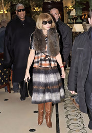 Anna Wintour paired her earth tone ensemble with cognac leather knee high boots.