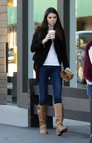 Kendall Jenner took a coffee break in a pair of medium rinse skinny jeans and tan riding boots.