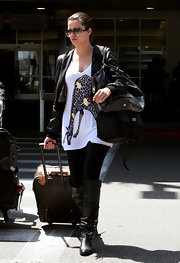 Khloe is carrying her essential travel companion, her LV monogram suitcase.
