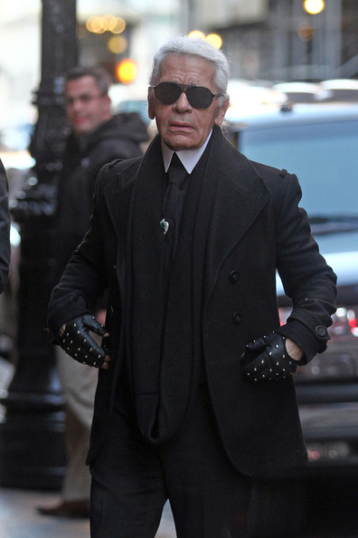 Karl paired his black trench coat with studded fingerless gloves.