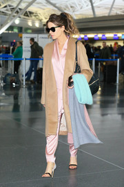 Kate Beckinsale layered a tan Ryan Roche wool coat over a pink satin pantsuit for a flight.