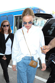 Kate Bosworth accessorized with a chic Rochas leather bag, featuring a crystal R embellishment and a gold chain strap, while catching a flight out of LAX.