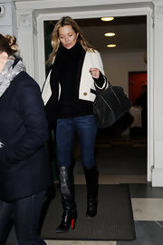 Kate Moss bundled up for the chilly weather in a cream jacket paired with classic black leather knee-high boots.
