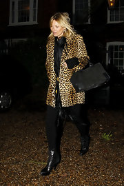 Kate Moss accessorized her ensemble with black lace-up ankle boots.
