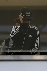 Katy Perry wore a black Adidas baseball cap to match her track jacket while catching a flight.