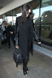Kendall Jenner completed her edgy airport look with black Chanel thigh-high boots with metal toe caps.