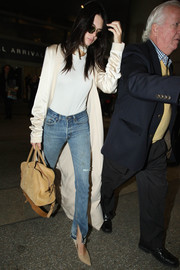 Kendall Jenner teamed her coat with ripped blue jeans by Re/Done.