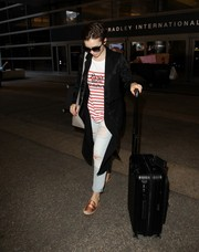 For her travel bag, Lily Collins chose a black rollerboard by Rimowa.