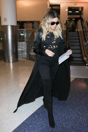 Khloe Kardashian turned heads at LAX in a tattered black top layered under a duster.