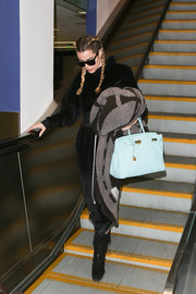 Khloe Kardashian bundled up in a black velour hoodie for a flight.