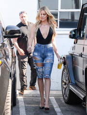 Khloe Kardashian put on a racy display in a deep-V black bodysuit by Flynn Skye while visiting a Van Nuys studio.