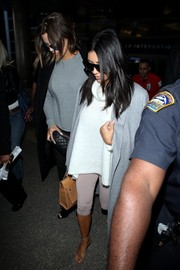 Kim Kardashian kept cozy in a loose white turtleneck and a gray coat for a flight.
