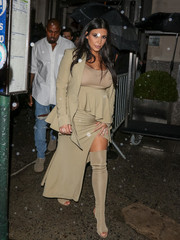 Kim Kardashian frilled up her baby bump in a beige peplum skirt suit by Givenchy for Rihanna's party.