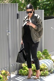 Kim Kardashian tempered her cleavage-baring top with an olive-green bomber jacket while visiting a salon.
