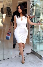 Kim Kardashian sheathed her curves in a tight-fitting white peplum dress with a cleavage-baring keyhole neckline for a trip to her store.