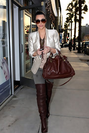 Kim K. totes a Paraty shoulder bag in rich brandy leather to match her thigh-high boots.