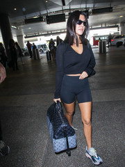 Kourtney Kardashian looked ready for a workout in her black bike shorts while catching a flight out of LAX.