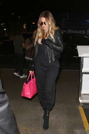 Khloe Kardashian teamed a black leather jacket with a bodysuit and sweatpants for a flight out of LAX.