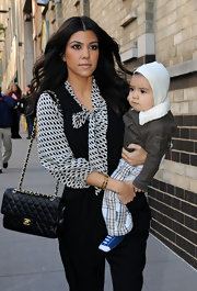 Kourtney kept her look classic while out and about with her son Mason. She paired her printed blouse and trousers with a timeless Chanel Flap bag.
