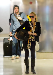 Kristin opted for comfy travel footwear, wearing leather knee-high boots.