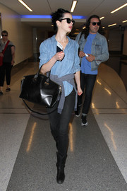 Krysten Ritter accessorized her airport look with a chic black leather tote by Alexander McQueen.