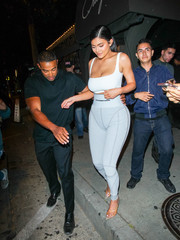 Kylie Jenner showed off her assets in a white sports bra by Naked Wardrobe while enjoying a night out.