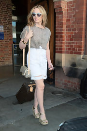 Kylie paired her dress shorts and blouse with a metallic quilted leather shoulder bag.