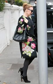 Kylie Minogue paired her Dolce & Gabbana coat with a classic leather purse.