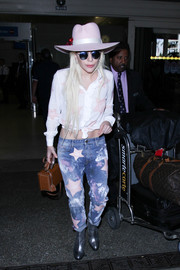 Lady Gaga styled her airport outfit with silver ankle boots by Saint Laurent.