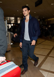 Taylor Lautner kept his cool at LAX in a retro navy bomber jacket and jeans.