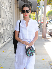 Lily Aldridge paired a floral-embroidered purse with a white shirtdress for a day of shopping.
