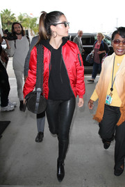 Lily Aldridge was tough-chic in a red bomber jacket by Unravel, teamed with black leather skinnies, while catching a flight at LAX.