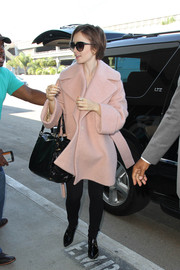Lily Collins finished off her travel outfit with a pair of black patent boots.