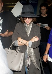 Lily Collins matched a Zadig & Voltaire skull-print scarf with a suede coat for a flight out of LAX.