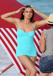 Adriana Lima models a bright blue ruched halter one-piece.