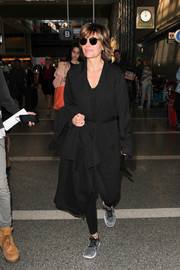 Lisa Rinna covered up with a black duster while catching a flight.