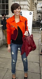 Frankie Sandford's orange motorcycle jacket brightened up the singer's casual look during London Fashion Week.