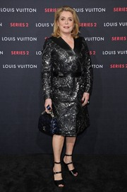 Catherine Deneuve attended the Louis Vuitton Series 2 exhibition wearing a sparkly black evening coat from the brand.