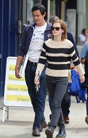 Emma Watson topped off her laid-back knit top and gray jean ensemble with on-trend lace up boots.