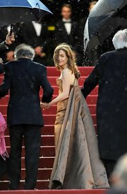 Isabelle Huppert made a dramatic entrance at the 'Love' premiere in a bronze evening dress with a voluminous train.