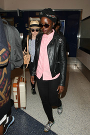 Lupita Nyong'o teamed a black leather jacket with a pink shirt and skinny jeans for a flight.